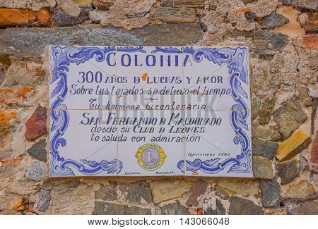 COLONIA DEL SACRAMENTO, URUGUAY - MAY 04, 2016: nice ancient ceramic sign with some colorfull letters hanging from a stone wall.