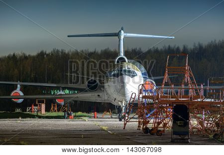 Old unused large passenger plane on a concrete strip at night. Front view on the forest background in racks and ladders environment.