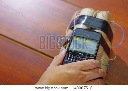 human hand checking if the cellphone is well conected to the set of explosives.