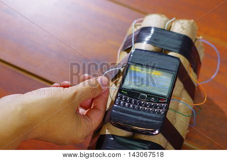 hand connecting the cable of the explosives to the cellphone.
