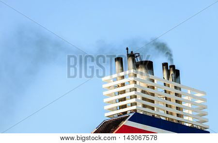 Naval maritime sea concept. Vessel chimneys releasing smoke. Ship part blue sky background.