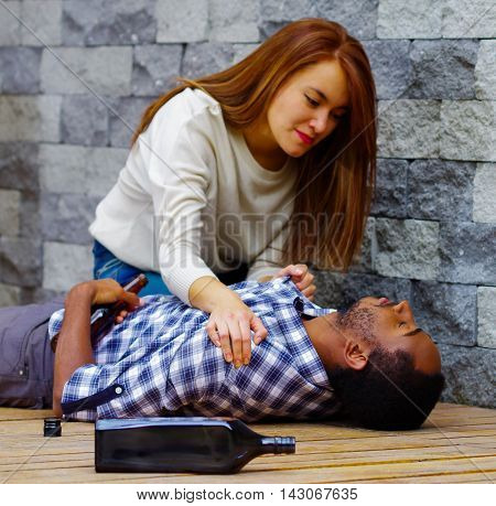 Man wearing casual clothes lying drunk passed out on wooden surface, pretty woman sitting beside him trying to get contact by touching and shaking.