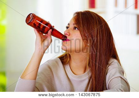 Attractive woman wearing white sweater sitting by bar counter drinking from beer bottle, drunk depressed facial expression, alcoholic concept.