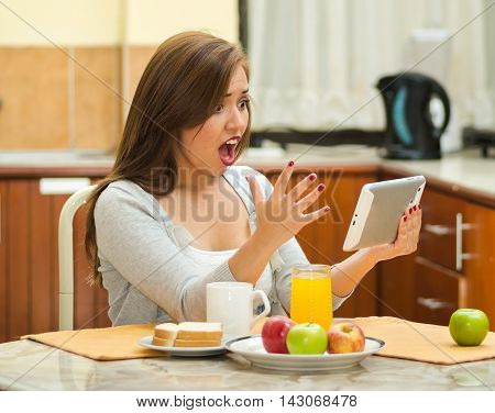 Young pretty brunette sitting by breakfast table looking at tablet screen, fruits, juice and coffee placed in front, hostel environment.