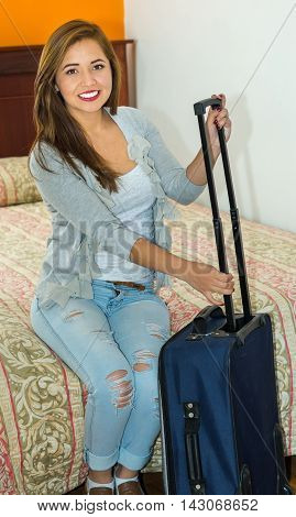 Young pretty hispanic woman wearing casual clothes sitting on bed holding onto suitcase handle, hostel guest concept.