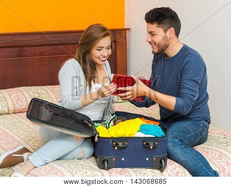 Young charming hispanic couple wearing casual clothes sitting on bed packing into suitcase together, hostel guest concept.