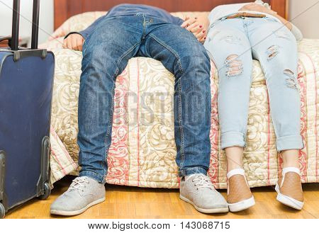 Closeup legs couple wearing jeans, sitting on edge of bed, blue suitcase standing beside, hostel concept.
