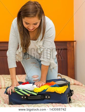Pretty young hispanic woman using her bodyweight pushing clothes into suitcase, hostel guest concept.