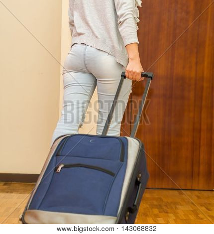 Legs of woman wearing casual pants walking towards door pulling blue suitcase, hostel guest concept.