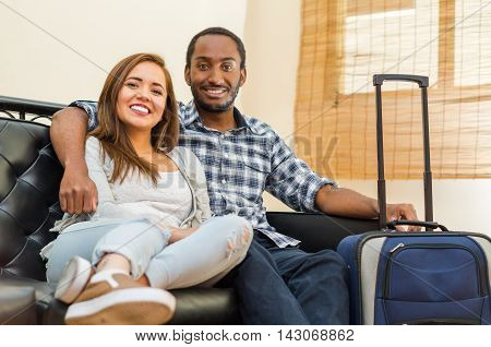 Charming young couple wearing casual clothes sitting down embracing and posing for camera smiling, blue suitcase standing on floor, hostel guest concept.