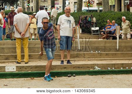 Barcelona, Spain 16 august 2016: old men playing petanque in a city park on Passeig de San Joan in Eixample
