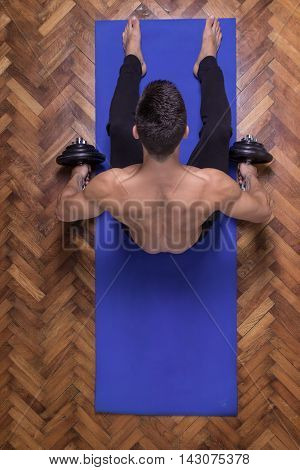 Young man dumbbell elevated view back rear