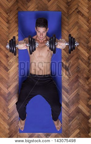 Young Man Dumbbell Flies Chest Abs Elevated View