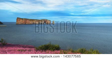 Beautiful view of The Rocher Perce with pink flowers in Perce city, Gaspesie in Quebec province.