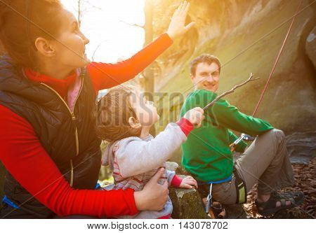 Young family outdoors is climbing on the rocks during the holidays.