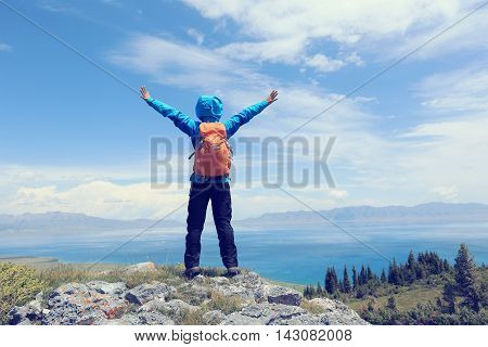 cheering young woman hiker open arms on mountain peak
