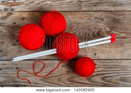 Natural woolen yarn and knitting on  wooden background