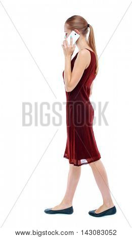 side view of a woman walking with a mobile phone. back view of girl in motion.  backside view of person.  Rear view people collection. Isolated over white background. The girl in the maroon sleeveless