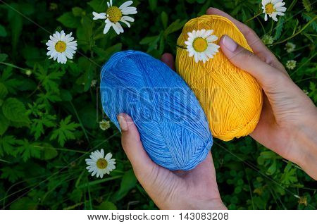 Female Hands Holding Two Balls Of Cotton Yarn On A Background  Green Grass