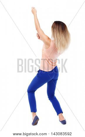 back view of standing girl pulling a rope from the top or cling to something. girl  watching. Rear view people collection.  backside view of person.  Isolated over white background. Blonde in blue