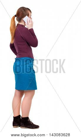 back view of a woman talking on the phone.  backside view of person.  Rear view people collection. Isolated over white background. Girl with red hair tied in a ponytail is standing sideways and