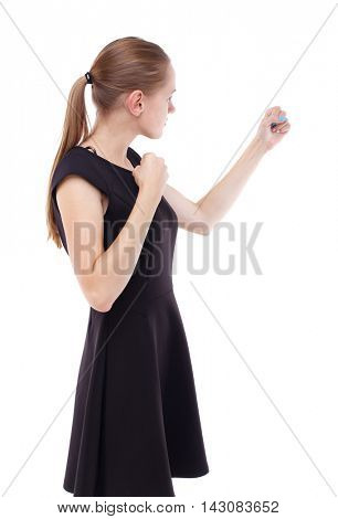skinny woman funny fights waving his arms and legs. Isolated over white background. Blonde in a short black dress clenched her fists.