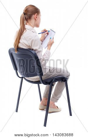 back view of young beautiful  woman sitting on chair and  takes notes in a notebook.  girl  watching. Rear view people collection.  backside view of person.  Isolated over white background. Skinny
