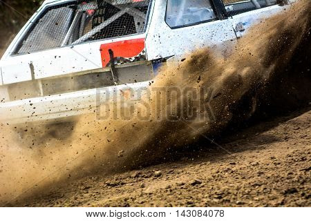Autocross on a dusty road. Close-up of car in competition up road on a dirt road. Powerful auto throws dirt