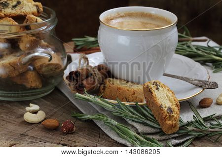 coffee with milk and sugar cookies with raisin on a wooden table