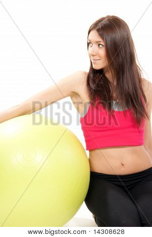 Slim Female Fitness Instructor With Ball In Gym