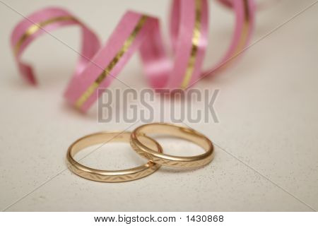 Two Wedding Rings Lay On A Light Background
