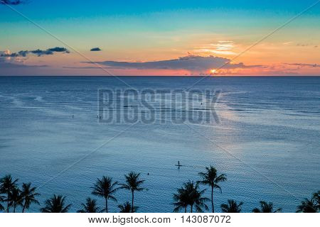 Paddle boarders enjoying a tropical island sunset .