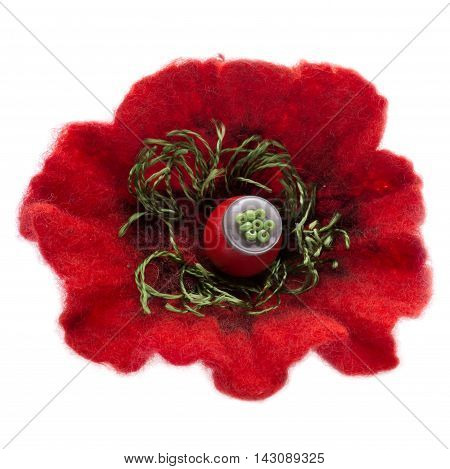 Brooch made of felt wool in the form of a poppy on a white background