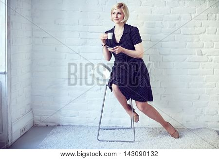 Retro styled young woman sitting on chair, drinking coffee.
