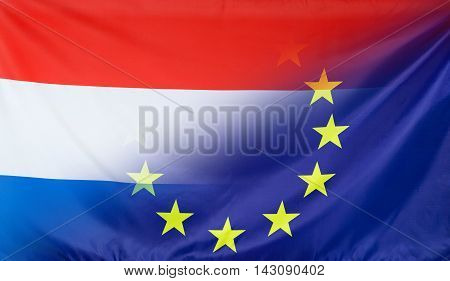 Netherlands and European Union relations concept with diagonally merged real fabric flags
