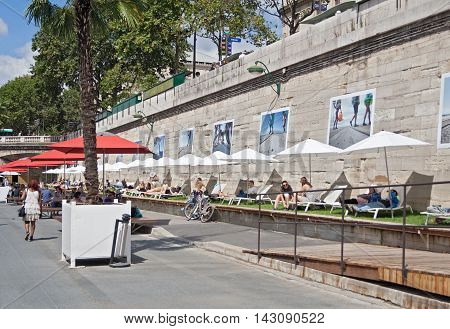 PARIS, FRANCE - AUGUST 6, 2016: people lying in the sun on the banks of the seine in paris