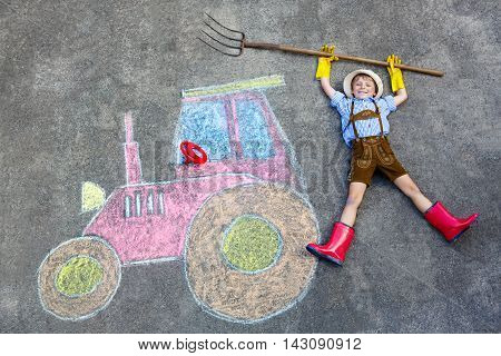 Happy little kid boy in straw hat and rain boots having fun with tractor picture drawing with colorful chalks. Children, lifestyle, fun concept. child dreaming of future and profession.