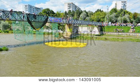 CLUJ-NAPOCA ROMANIA - AUGUST 14 2016: Rubber duck race down the river for charity purposes. Yellow toy ducks are floating on the water.