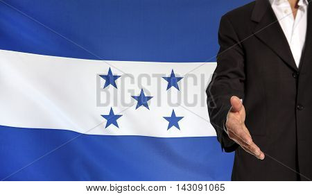 Businessman with an open hand waiting for a handshake concept for business with the Honduras flag in the background