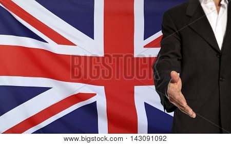 Businessman with an open hand waiting for a handshake concept for business with the Great Britain flag in the background