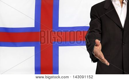 Businessman with an open hand waiting for a handshake concept for business with the Faroe Islands flag in the background