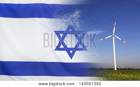 Concept clean energy with flag of Israel merged with wind turbine in a blue sunny sky and green grass with flowers
