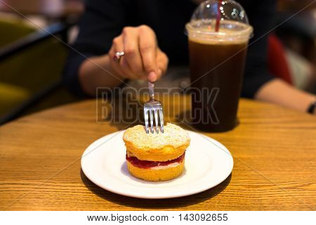 Selected Focus woman holding fork eating scone with iced coffee on the table