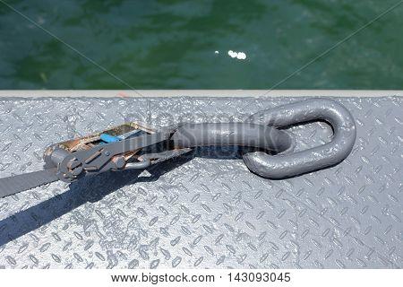Metallic mooring ring on metal floor on dock