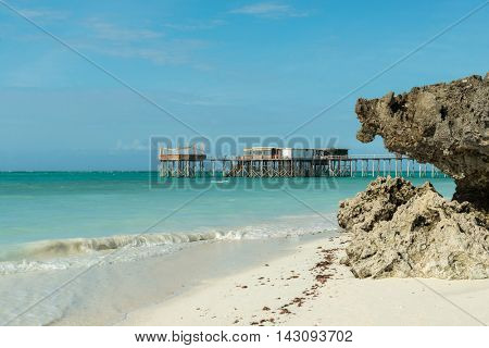 colorful view of wooden pier in ocean and horizon from beach in Zanzibar