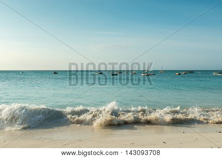 foamy wave on Zanzibar beach with fishing boats in turquoise ocean and horizon on the background