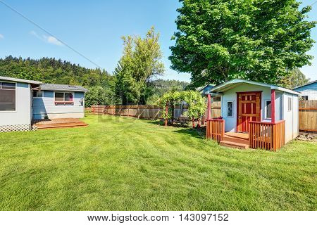 Fenced Backyard And Hanging Swing With Nice Landscape Desing.