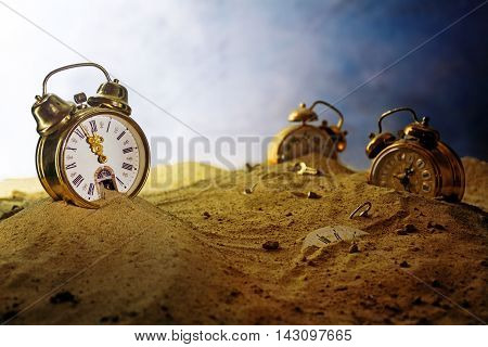 sand running out of a nostalgic alarm clock other watches sink into the sand surreal metaphor in a fantasy landscape concept of time passes by eventide or infinity selected focus very shallow depth of field