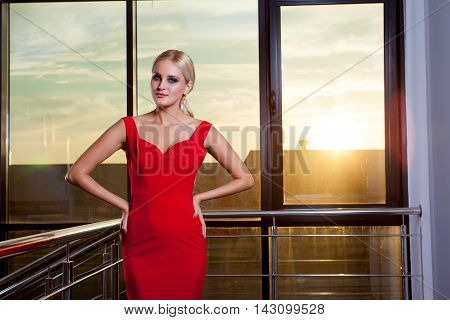 Young beautiful glamorous blonde girl in a red dress posing on the background of glass showcase.