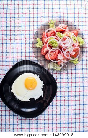 Surface Of The Table With A Black Plate With A Fried Egg And A Tomato Salad